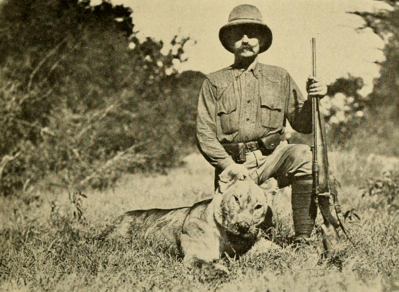 in an old sepia photo a person in a pith helmet holding a gun kneels next to a dead animal