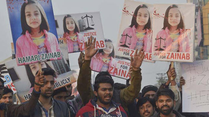 image shows protestors holding placards at death of Zainab Ansari