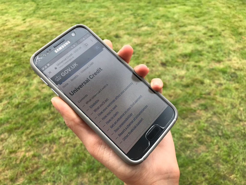 a hand holds a phone which displays the homepage for Universal Credit
