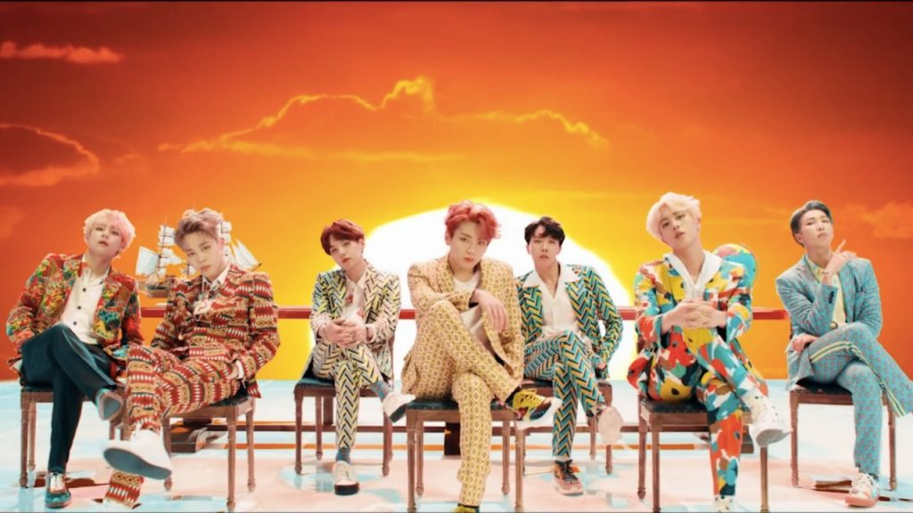 BTS sit on chairs in their music video for idol idol