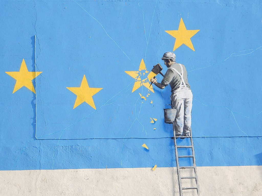 street art depicts a person in dungarees dismantling the EU flag