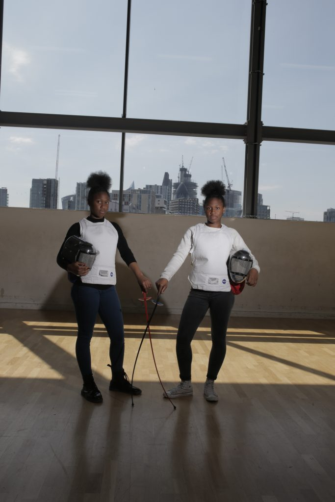 two girls wearing fencing outfits stand side by side