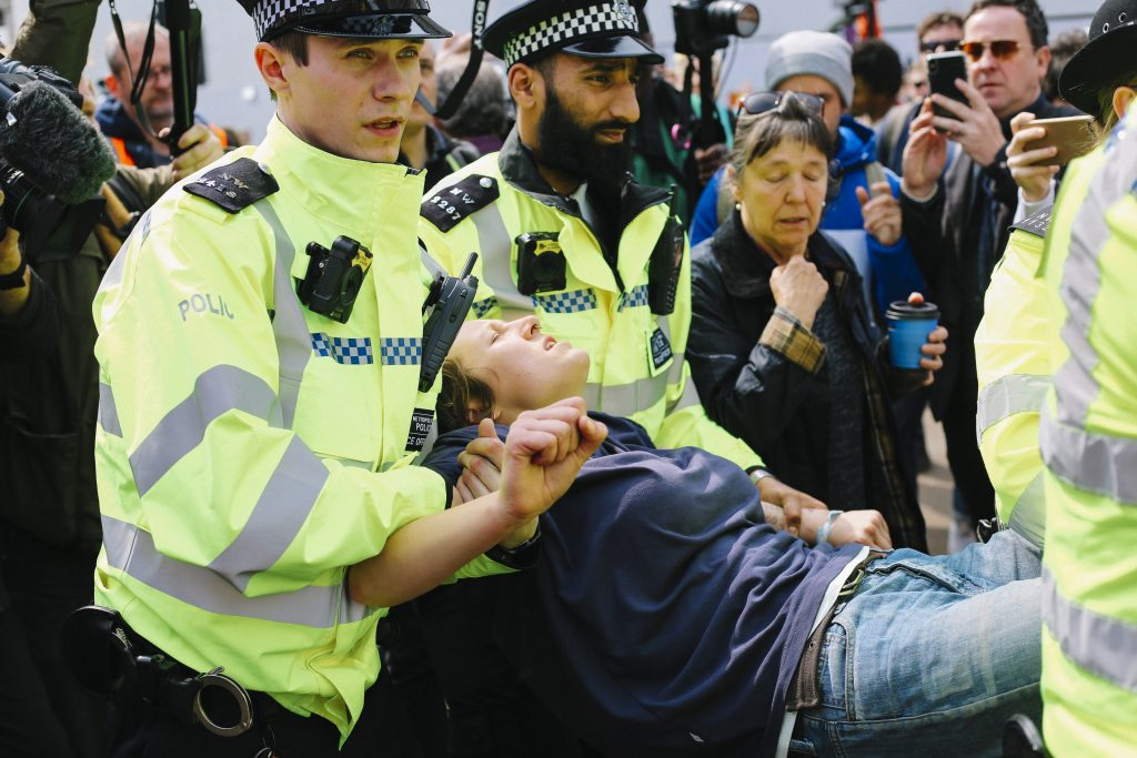 a person is detained by police in high vis jackets