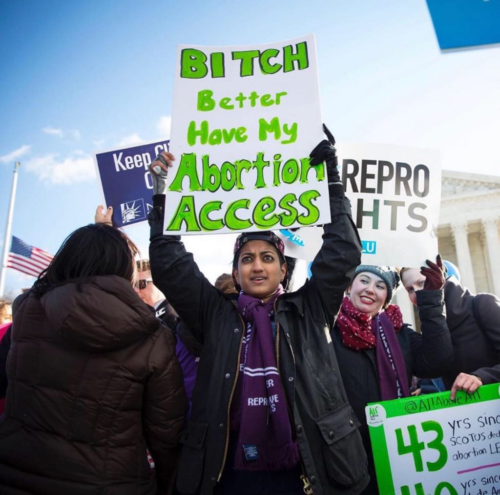 a person holding a placard at a pro-choice protest