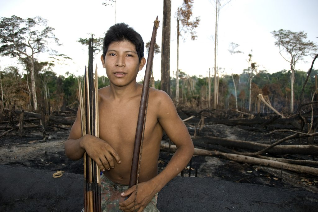 Hemokoma'á stands in smouldering forest in the Awá territory of the Amazon