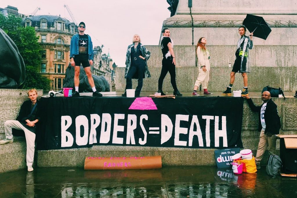 "protestors stand above a banner that reads ""borders equals death"""