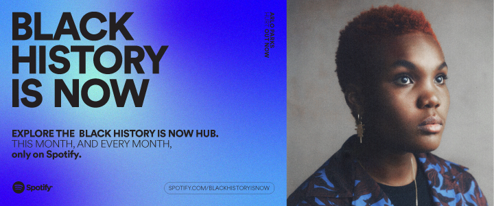 "Advert for Spotify's ""Black History Is Now"" hub on the Spotify app and website. Click the link to visit their hub featuring black musicians and podcasters. The image in the ad shows a photograph of Arlo Parks looking to the right of the frame, with cropped red tinted afro hair, and wearing a brown and blue printed jacket, and wearing gold earrings, one is shaped like an alligator. The advert features a blue and teal graphic that the text is overlaid onto."