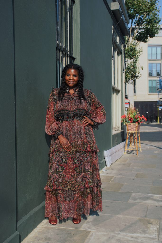an image of hair stylist Charlotte Mensah stood in an autumnal coloured dress, she is smiling and has her hair in long chunky twists