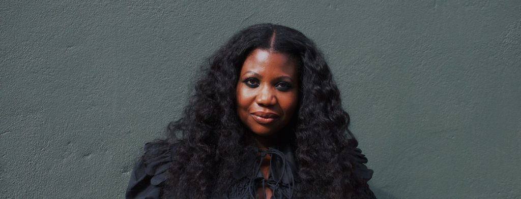 an image of Charlotte Mensah with long wavy hair set against a dark green background, she's wearing a black top