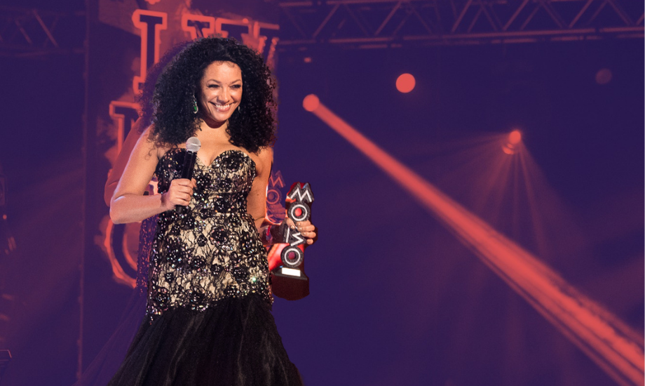 An image of MOBO Awards founder Kanya King, holding an award dressed in a black gown. Her image is superimposed against a red duotone stage, with a spotlight shining across.