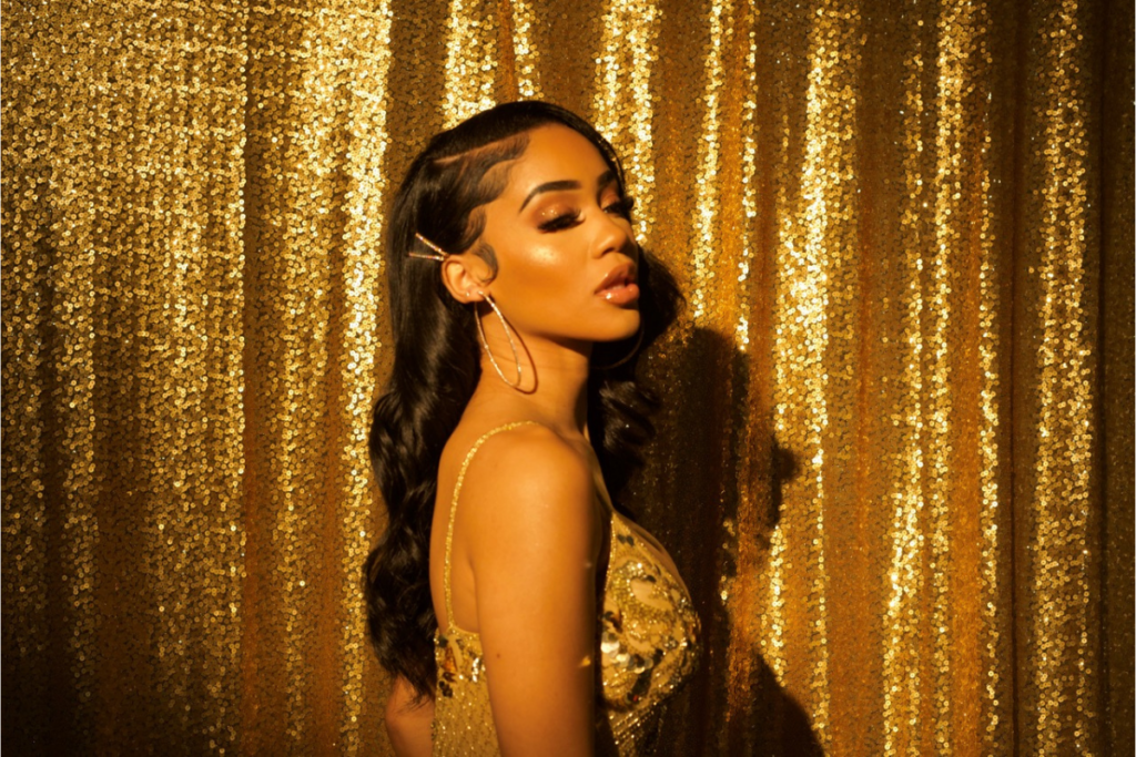 A photo of rapper Saweetie against a sparkly gold backdrop. Her long black hair is in loose waves and she's wearing hoop earrings and a sequinned light gold top.