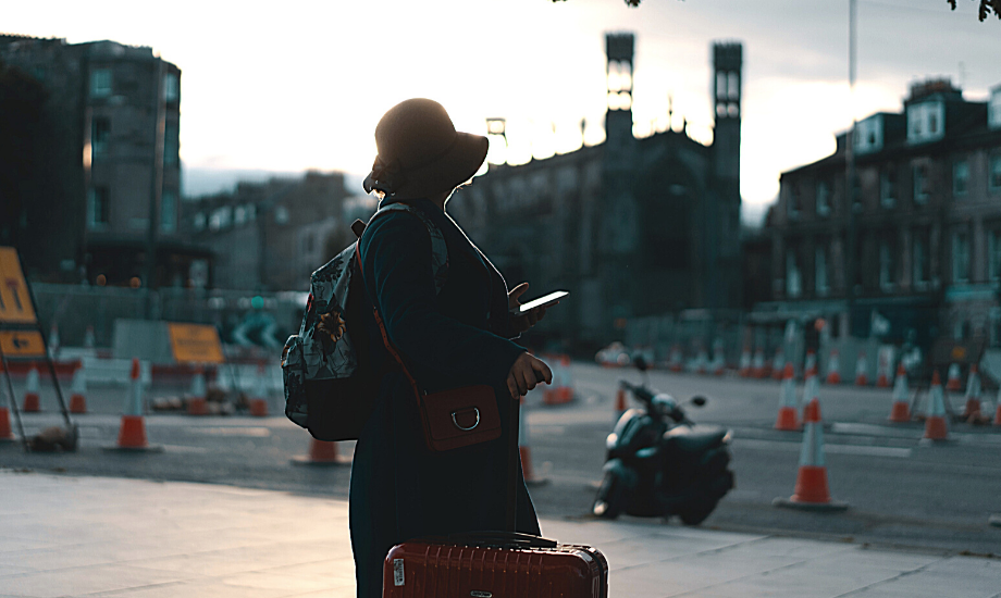 A woman with a suitcase stands silhouetted against a street