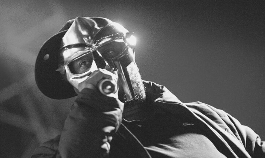 A Wikimedia Commons image of MF Doom on stage wearing a gold mask and holding a mic, in black and white. For a Five on it dedicated to the late rapper.